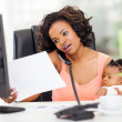African american woman with baby girl working from home — Lizenzfreies Foto