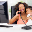 African businesswoman talking on landline phone while holding ba — Stock Photo