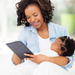 Young african mother using tablet computer at home — Stock Photo