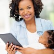 Young african mother holding tablet computer — Stock Photo