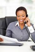 African american office worker talking on landline phone — Stock Photo