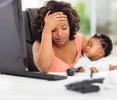Frustrated african american businesswoman with baby in office — Stock Photo