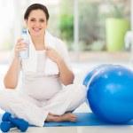 těhotná žena drží láhev vody — Stock fotografie