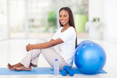 Afro american woman sitting on mat after working out — Stock Photo