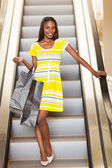 Shopping african woman using escalator — Stockfoto