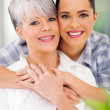 Stock Photo: Daughter hugging middle aged mother