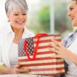 Young woman giving her senior mother a gift — Stock Photo