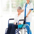 Stock Photo: Young nurse pushing middle aged patient on wheelchair