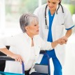 Medical nurse helping senior woman on wheelchair — Stock Photo