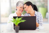 Happy middle aged woman and adult daughter using laptop — Stock Photo