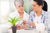Adult daughter helping senior mother with her finances — Stock Photo