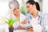 Young woman helping mother sorting out her finances — Stock Photo