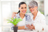 Senior mother helping daughter calculate her finances — Stock Photo