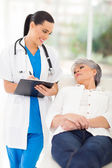Medical doctor consulting senior patient in office — Stock Photo