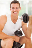 Cheerful young man working out with dumbbells — Stock Photo