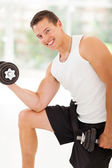Muscular man lifting weights — Stock Photo