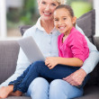 Little girl sitting on grandmother's lap with notebook computer — Stock Photo #32771829