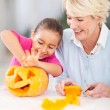 Stock Photo: Little girl cleaning her halloween pumpkin with granny