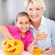 Little girl and grandmother making halloween pumpkin — Stock Photo