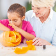 Stock Photo: Granddaughter helping grandmother making halloween pumkin