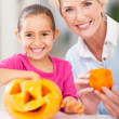 Stock Photo: Grandmother and granddaughter making halloween pumpkin