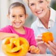 Grandmother and granddaughter making halloween pumpkin — Stock Photo