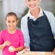 Little girl and granny baking at home — Stock Photo
