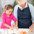 Granddaughter and grandmother baking cookies together — Stock Photo #32774633