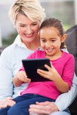 Cute little girl using tablet pc with grandma — Stock Photo