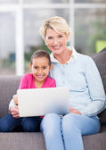 Senior woman and her granddaughter using laptop — Stock Photo