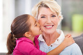 Cute granddaughter kissing her grandmother — Stock Photo