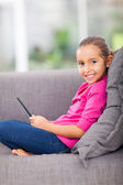 Little girl holding tablet computer sitting on sofa — Stock Photo