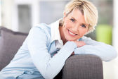 Pretty senior woman relaxing on a couch — Stock Photo