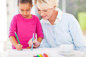 Grandma teaching granddaughter drawing — Stock Photo