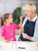Little girl feeding gingerbread cookie to her grandmother — Stock Photo