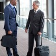 Businessmen talking at airport — Stock Photo