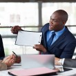 Young african american businessman presenting figures at a meeti — Stock Photo #34109107