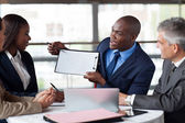 Young african american businessman presenting figures at a meeti — Stock Photo