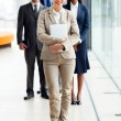 Young businesswoman standing in front of colleagues — Stock Photo