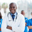 African american medical doctor with colleagues in background — Stock Photo #34178471