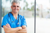 Middle aged surgeon with arms folded — Stock Photo