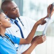 African doctors looking at patient's x-ray — Stock Photo #34181111