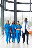 Group of health care workers walking in hospital — Stock Photo