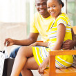 Young african couple sitting on public bench — Stock Photo