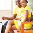 Young african couple sitting on public bench — Stock Photo #34422429