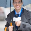Young journalist working outdoors in the rain — Stock Photo