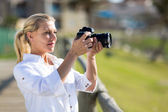 Middle aged woman taking photos outdoors — Stock Photo