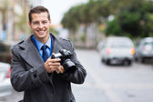 Journalist holding a camera in the city — Stock Photo