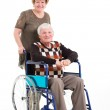 Disabled old man sitting on wheelchair with caring wife — Stock Photo #35221571