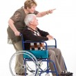 Stock Photo: Senior woman behind disabled husband and pointing